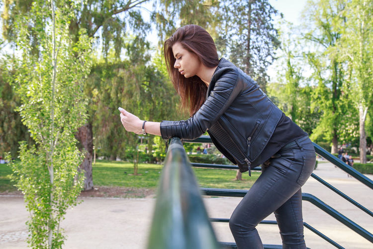 Young woman in black leather jacket holding smartphone and leaning on fence looking at camera in park. Casual Fashion Leather Lifestyle Nature Standing Student Stylish Woman Young Black Candid Device Female Gadget Girl Jacket Park Portrait Seasonal Smart Phone Street Style Technology Trendy