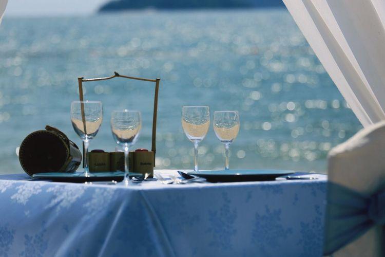 Wineglasses on table against lake