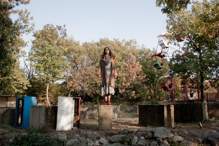 Full Length Of Woman Standing On Built Structure Against Trees
