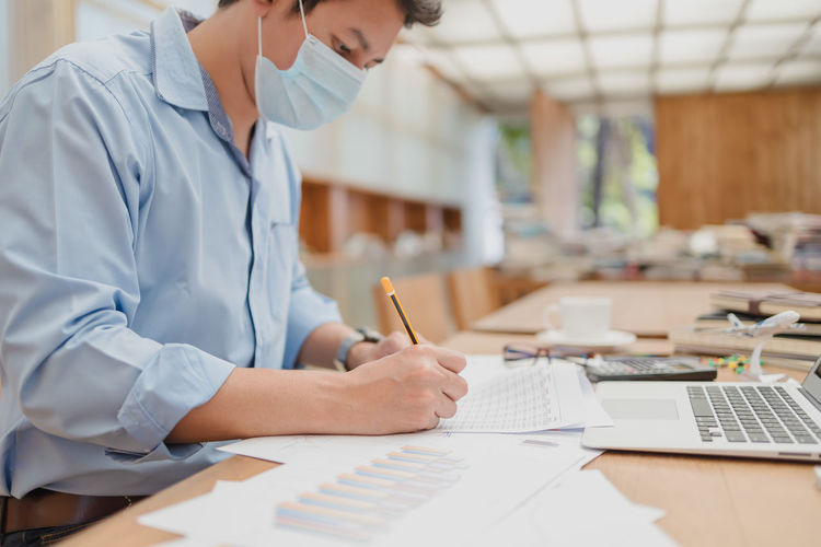 Midsection of wearing mask businessman writing on paper at office