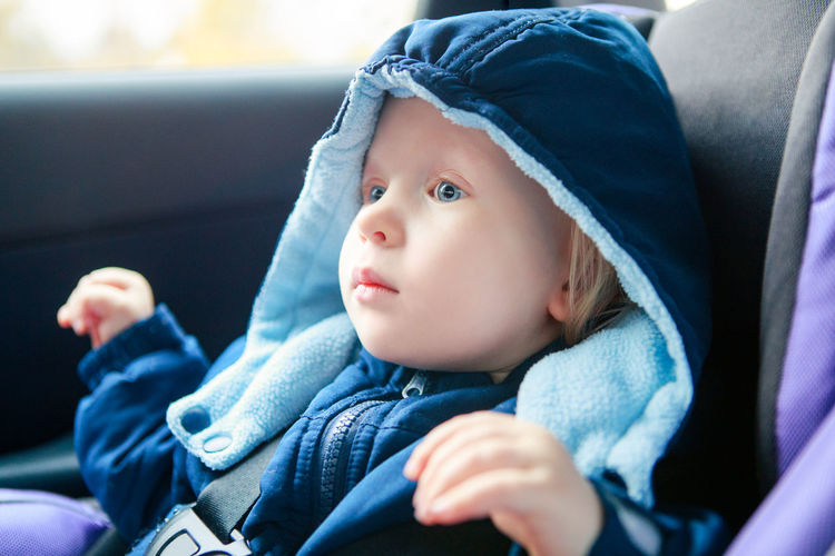 Baby infant sitting in car seat. kid in outwear clothes in carsit fastened with seatbelt.