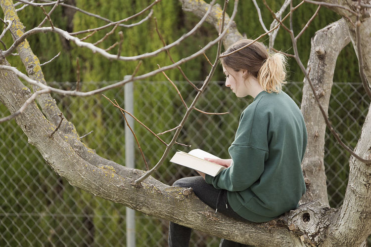 Woman reading book while sitting on tree trunk