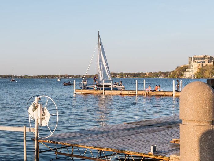 People getting ready to sail on Lake Mendota. Sailboat Water Transportation Nautical Vessel Sea Architecture Nature Sailboat Mode Of Transportation Sky Travel Day Clear Sky Travel Destinations Outdoors Sailing