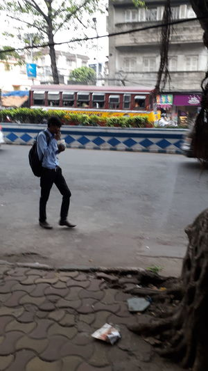 Full length of man walking on footpath in city