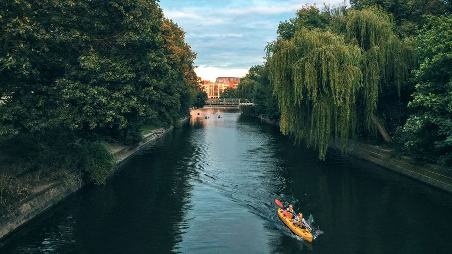 People Kayaking On Canal Amidst Trees