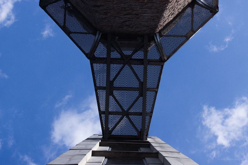 Directly below shot of building against blue sky