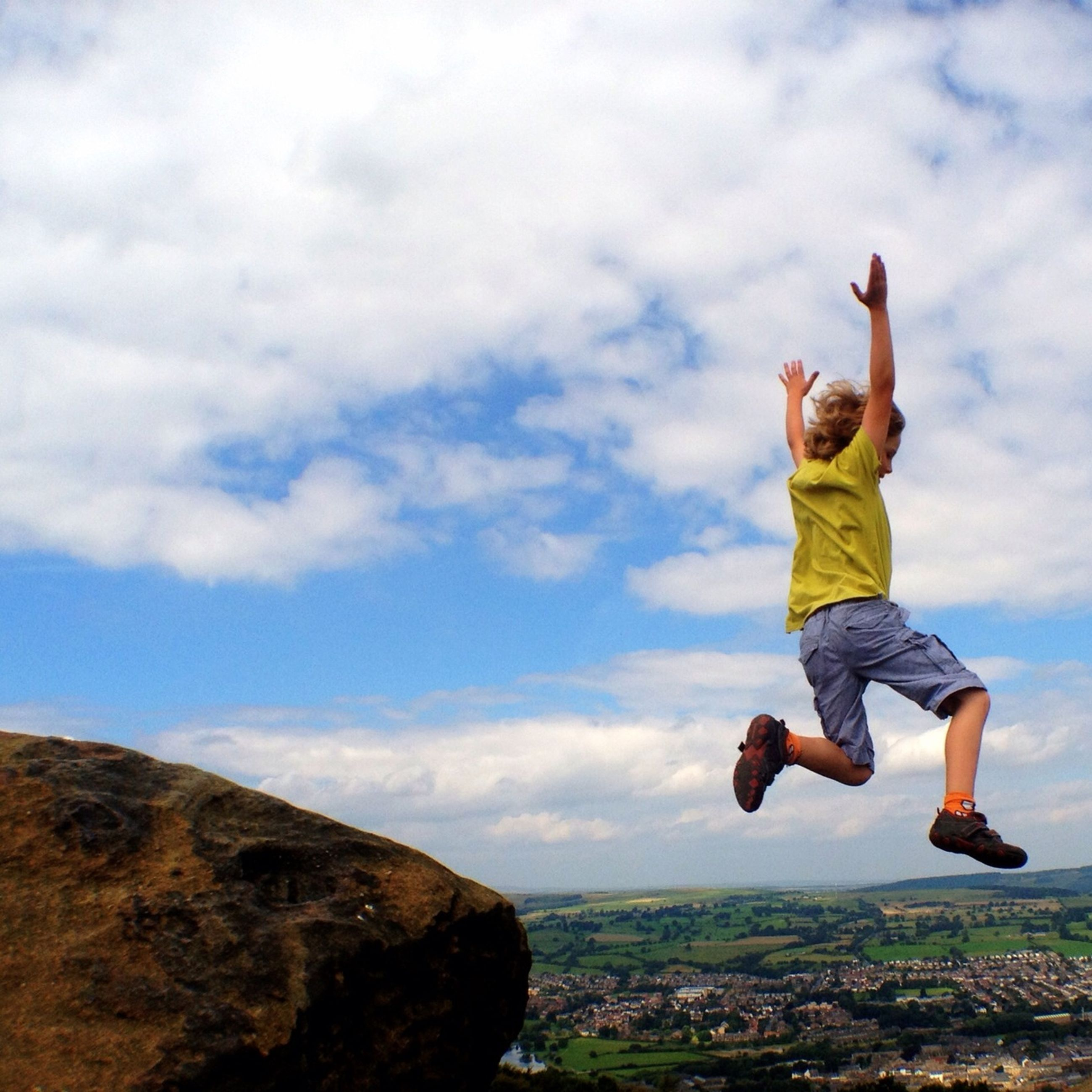 lifestyles, full length, leisure activity, sky, casual clothing, cloud - sky, standing, arms outstretched, carefree, freedom, jumping, men, cloudy, mid-air, arms raised, cloud, balance, person