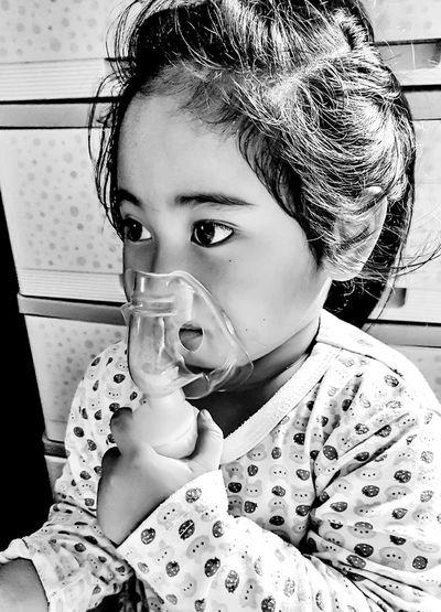 Girl looking away while wearing oxygen mask