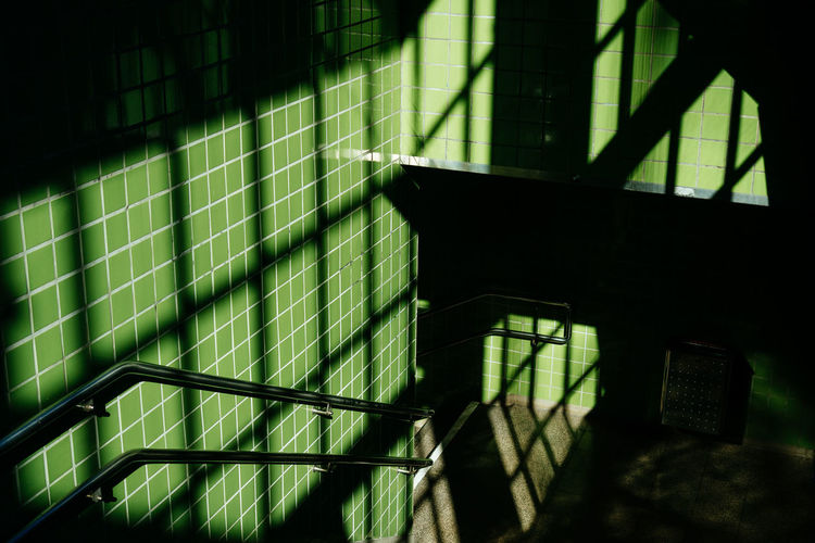 High Angle View Of Shadow On Green Tile Wall