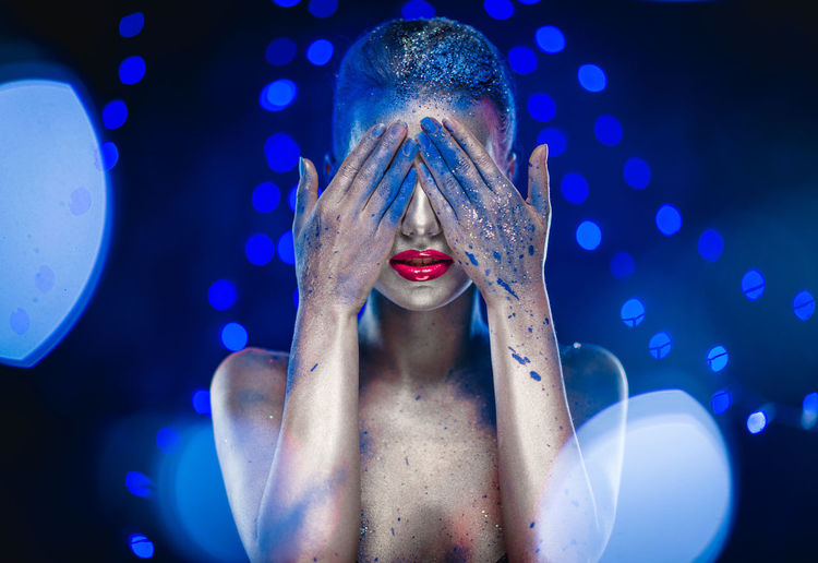 Naked Woman With Glitter Covering Her Eyes Against Blue Background