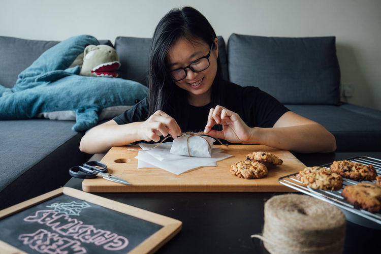 Smiling woman packing food sitting at home
