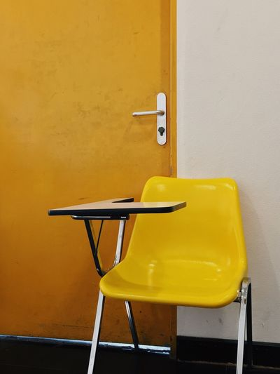 Yellow chair and brown door as background Brown Door Yellow Chair Yellow Wall - Building Feature No People Seat Chair Table Architecture Indoors  Building Built Structure Empty