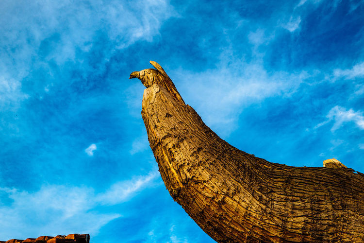 Low Angle View Of Wooden Sculpture Against Blue Sky