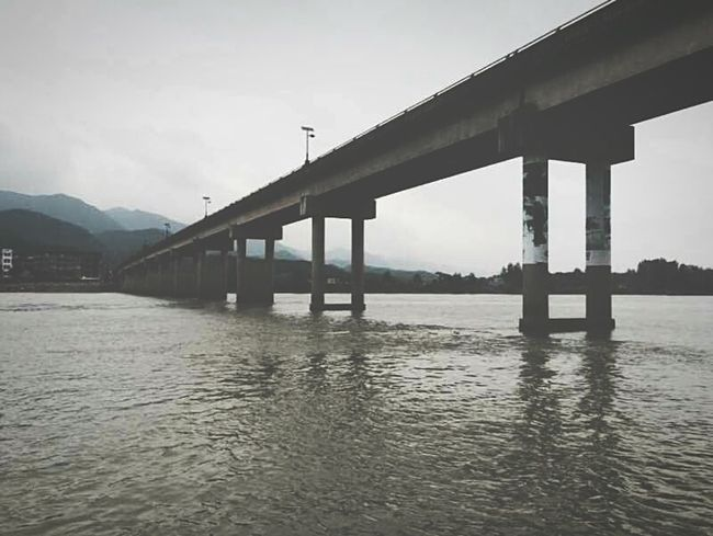 Bridge - Man Made Structure Built Structure Connection Architecture Engineering Water River Transportation Low Angle View Waterfront Architectural Column SUPPORT Sky Bridge Outdoors Nature Cloud - Sky No People Green Color Suspension Bridge
