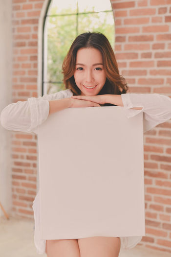 Adult Beautiful Woman Brick Brick Wall Brown Hair Front View Hairstyle Happiness Holding Lifestyles Looking At Camera One Person Portrait Smiling Standing Three Quarter Length Wall Wall - Building Feature Women Young Adult Young Women