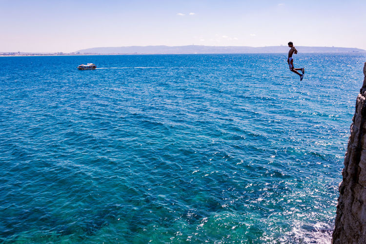 Man jumping off cliff into sea