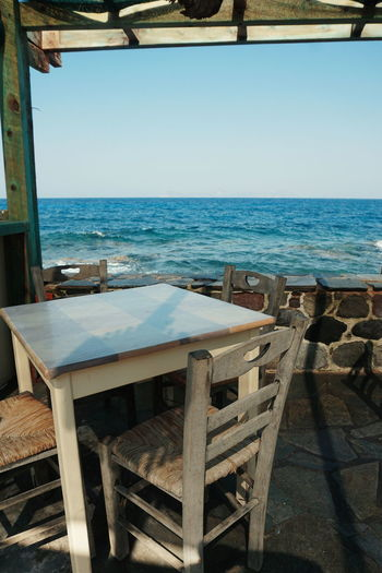 Greek taverna by the sea View Beach Chair Clear Sky Day Horizon Over Water Nature Nisyros No People No Person Outdoors Place Setting Reastaurant Scenics Sea Seascape Sky Table Table And Chairs Tables Taverna Tranquil Scene Tranquility Water Wood - Material