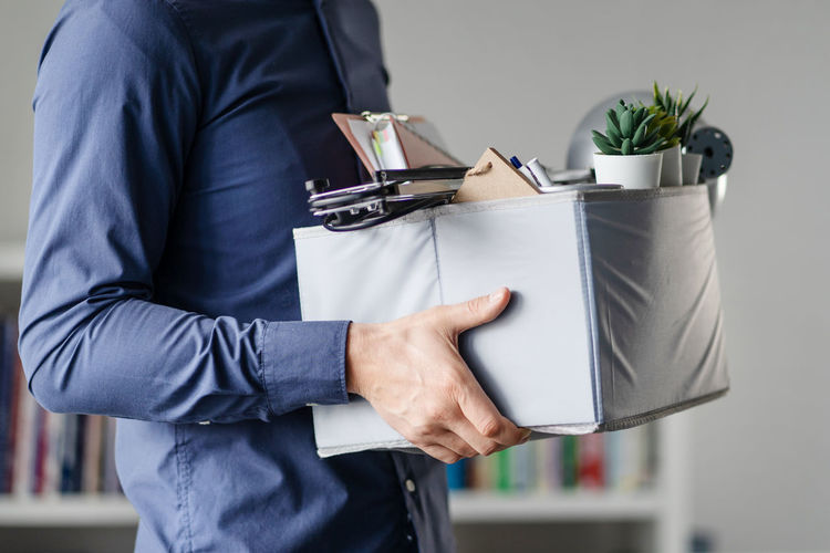 Midsection of man holding cardboard box in office