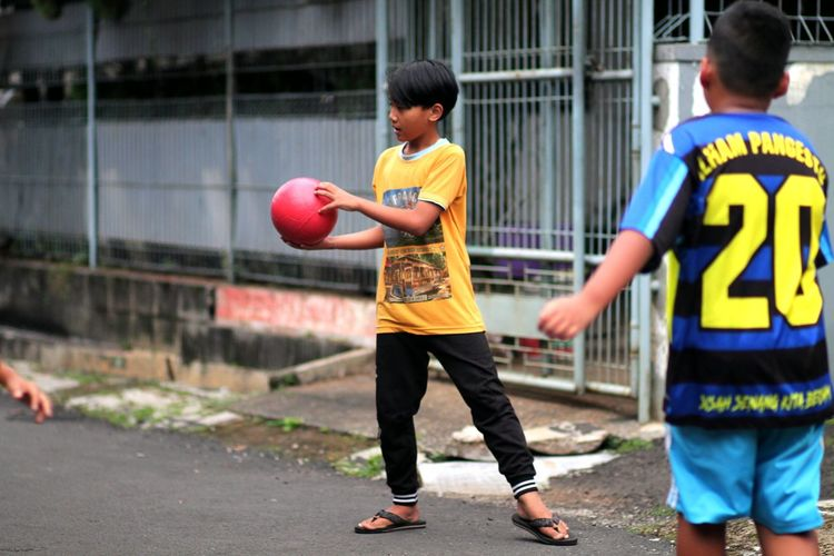Full length of boys playing with ball in city