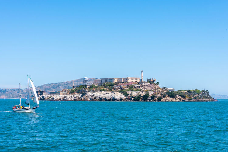Alcatraz Prison Sea Water Nautical Vessel Sailboat Transportation Blue Waterfront Mode Of Transportation Sailing Sky Clear Sky Day Nature Travel Copy Space Architecture Scenics - Nature Beauty In Nature Mast Yachting No People Outdoors