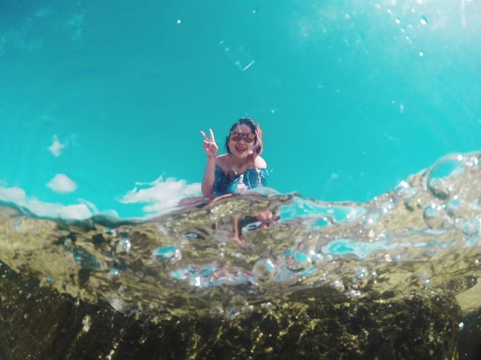 Portrait of woman gesturing seen through sea water