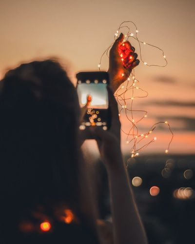 Rear view of woman photographing while holding illuminated string lights
