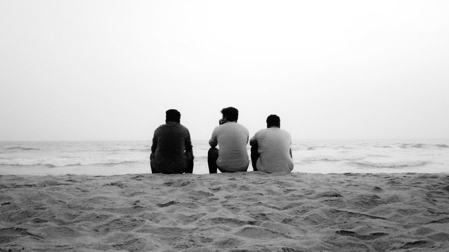 Rear view of friends sitting at beach against clear sky