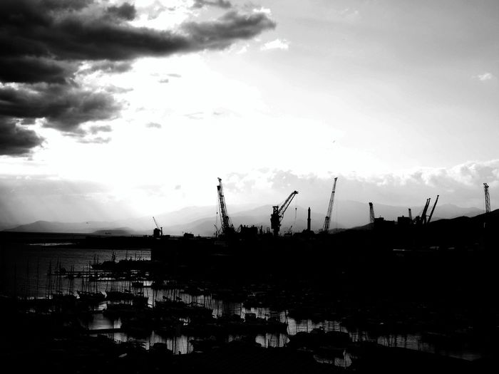 Cranes at harbor against cloudy sky