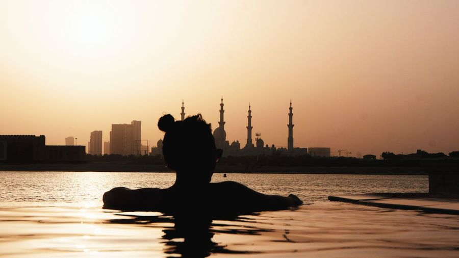Rear view of silhouette woman in infinity pool against sky during sunset