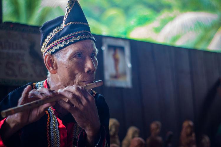 An old man from bidayuh group playing bamboo flute at Sarawak Culture Village Bamboo Flute Bidayuh Flute Long Hair Malaysia Nature Old Sarawak Sarawak Culture Village Traditional