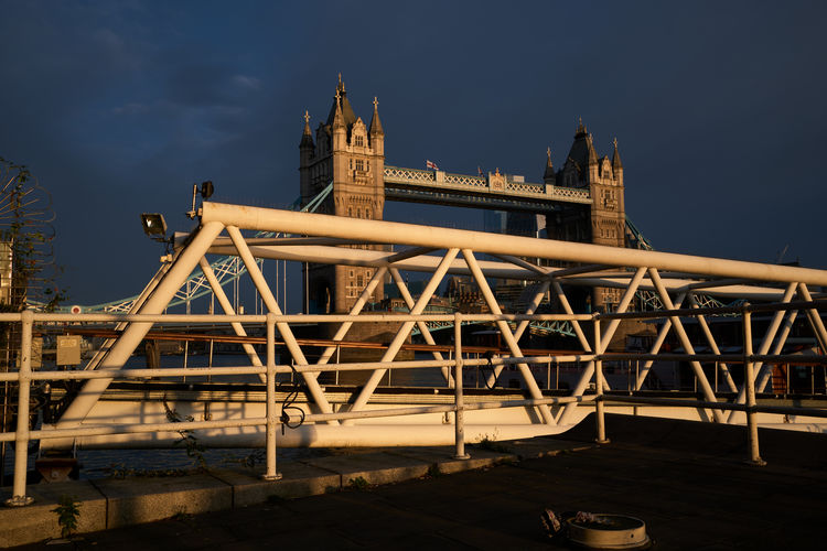 Low angle view of bridge over river by buildings against sky