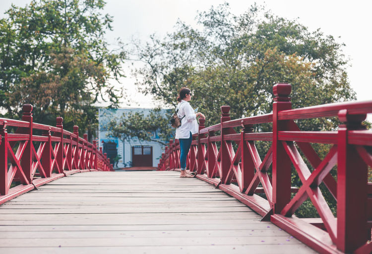 Hoan Kiem Lake. Bridge - Man Made Structure Day Footbridge Full Length Growth One Person Outdoors People Railing Real People Red Standing Tree Young Adult An Eye For Travel Analogue Sound