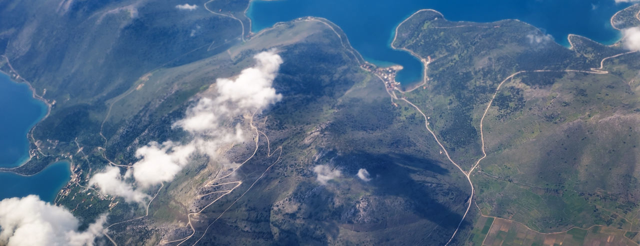 Aerial view of land and mountains against sky