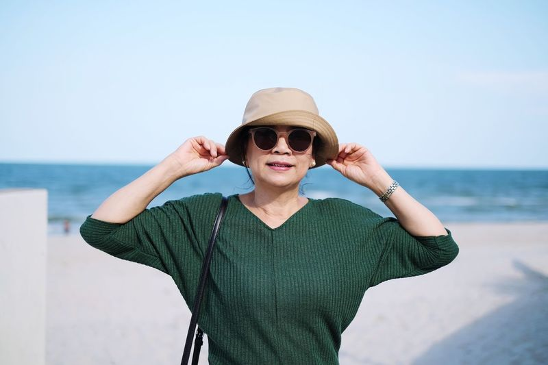 Portrait of woman wearing sunglasses and hat standing against sea