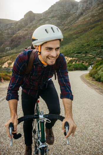 Portrait of smiling man riding bicycle on road