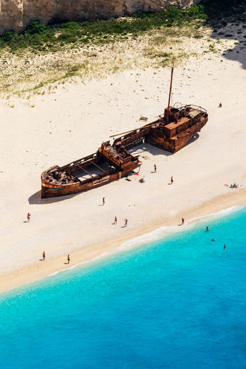 High Angle View Of People And Shipwreck At Beach On Sunny Day
