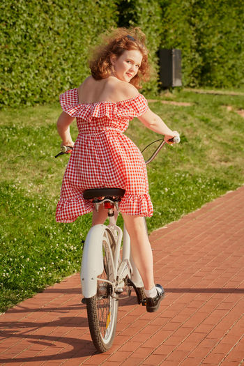 Full length of woman riding bicycle