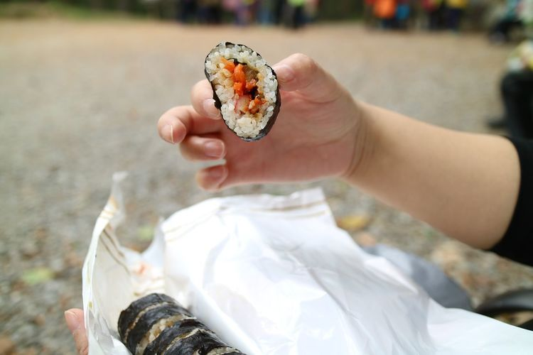 Cropped hands holding sushi