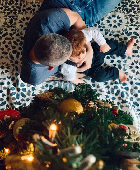 High angle view of father with son sitting by christmas tree at home
