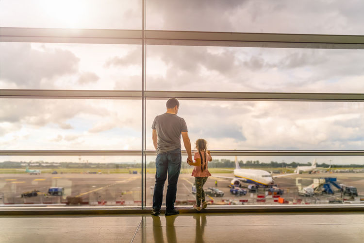 Rear view of men sitting at airport against sky