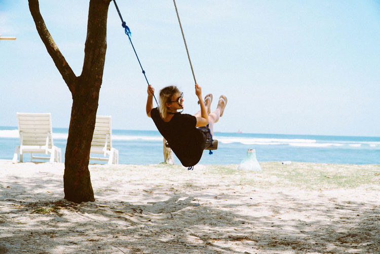 A girl on a swing at a beach. Swinging Beach Beachphotography Beauty In Nature Clear Sky Day Full Length Fun Horizon Over Water Leisure Activity Lifestyles Nature One Person Outdoors Paradise People Real People Scenics Sea Sky Swing Water Women Young Adult Young Women The Great Outdoors - 2018 EyeEm Awards