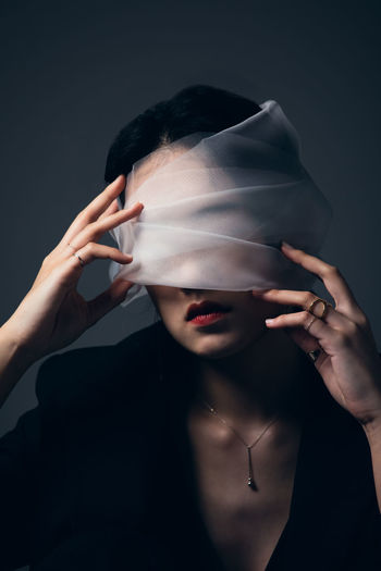 Portrait of young woman holding mask over black background