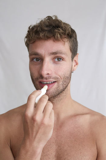 Portrait of handsome young man holding cigarette over white background