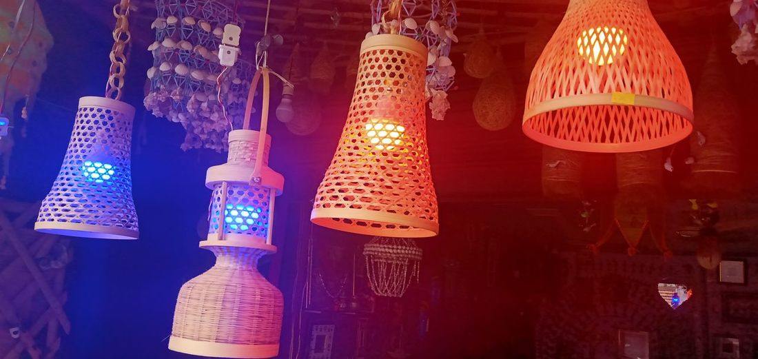 Illuminated lanterns hanging in store at night