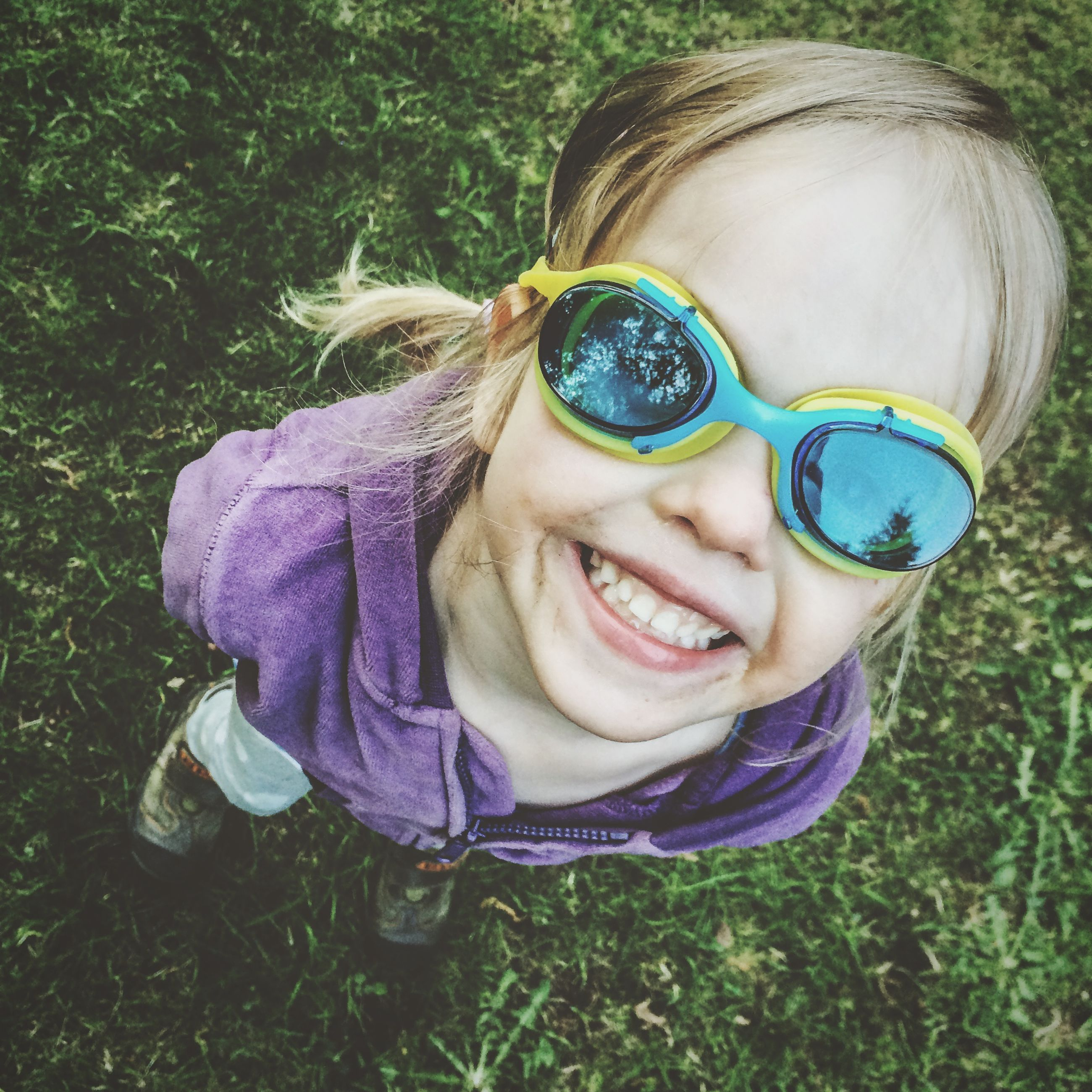person, looking at camera, portrait, childhood, smiling, lifestyles, leisure activity, elementary age, front view, innocence, happiness, cute, grass, headshot, girls, sunglasses, casual clothing, young adult