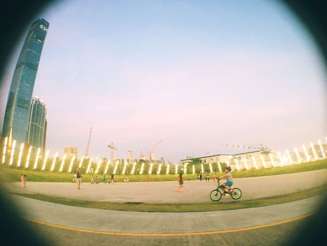 Streetphotography Streetphoto_color Streetart Grass Sky Twilight Sky Architecture Built Structure Outdoors Clear Sky Fish-eye Lens City People Cycling Boy Skyscraper Night Lights Evening Sky The Great Outdoors - 2017 EyeEm Awards Park - Man Made Space Cityscape Urban Geometry Urban Skyline Urbanphotography Art Is Everywhere