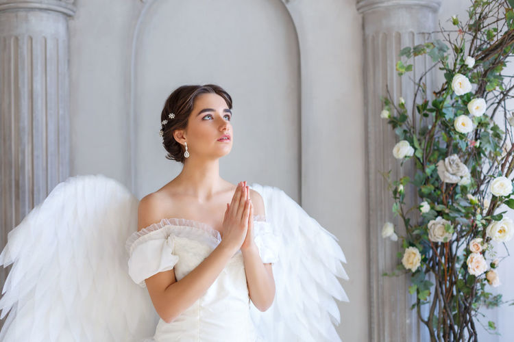 Portrait of a beautiful young woman in a white dress and angel wings, standing with a pleading