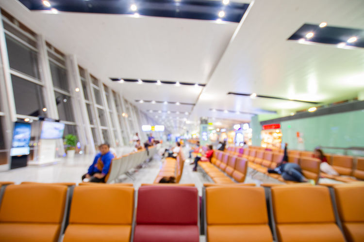 Seat Chair Indoors  Men Group Of People Illuminated Transportation In A Row Women Real People Adult Sitting People Mode Of Transportation Travel Ceiling Vehicle Seat Airport Crowd Architecture Airplane Seat Waiting