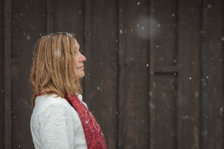 Young woman looking away while standing on snow