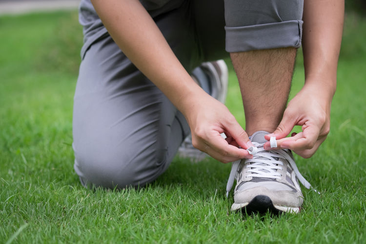 Low Section Of Man Tying Laces In Grass